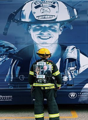 Firefighter in front of bus with photo