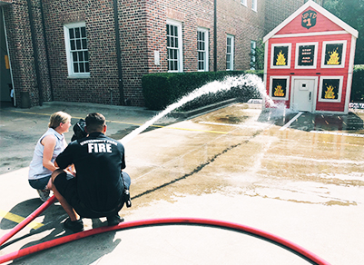 Firefighter shooting a hose into a play house