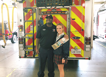 A firefighter and a girl scout in front of a fire truck