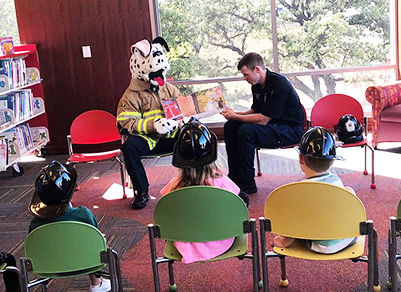 Firefighter and dalmatian costume reading to kids